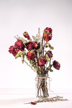 rose petals: Bouquet of red dried roses in glass vase on white background Stock Photo
