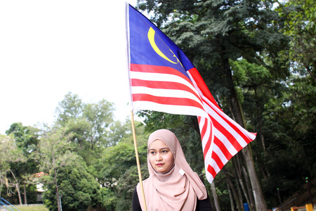 1malaysia: young muslim women holding a nation flag for a Malaysia independence day with happy reaction
