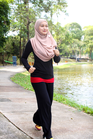 young muslim women was jogging around the lake in the morning with happy face reaction