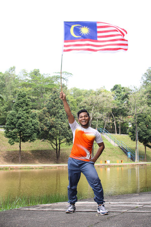 1malaysia: a man  holding a nation flag for a Malaysia independence day with happy face reaction
