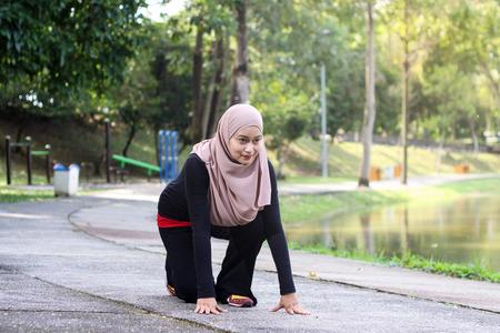 Atletische moslimvrouw op het spoor begint rond het park rond te lopen