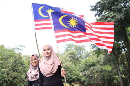 1malaysia: two young muslim woman  holding a nation flag for a Malaysia independence day with a happy face reaction Stock Photo