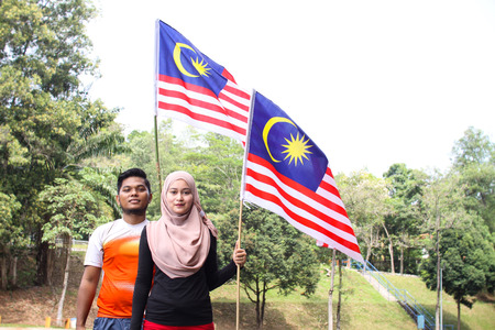 1malaysia: Cheerful couple friends  holding a nation flag for a Malaysia independence day with a happy reaction