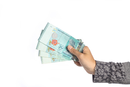 female hand holding two hundred ringgit malaysian money isolated on white background
