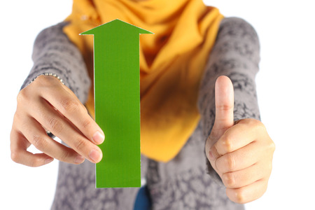 green arrow: female hand holds green arrow and showing thumbs up sign Stock Photo