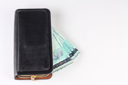 devaluation: black purse with malaysian money isolated on white background