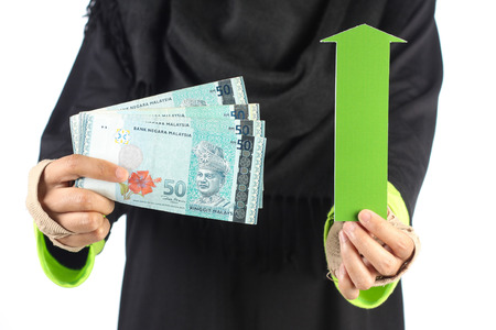green arrow: female hand holding pack of malaysian money with green arrow isolated on white background