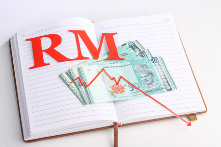 red arrow: malaysian money with red arrow and malaysia ringgit sign on notebook Stock Photo