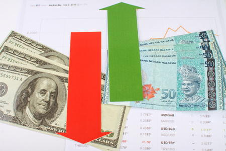 green arrow: malaysian and the united states of americas money with red and green arrow on fluctuating chart Stock Photo