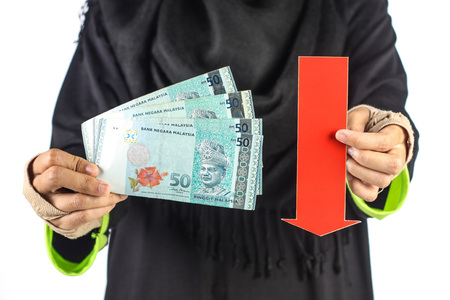 red arrow: female hand holding pack of malaysian money with red arrow isolated on white background Stock Photo