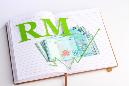 green arrow: malaysian money with green arrow and malaysia ringgit sign on notebook