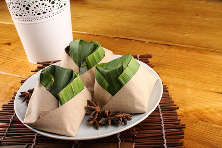 traditional fresh Malaysian nasi lemak packed with banana leaf in wood background