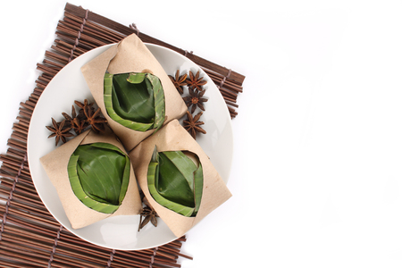 traditional fresh Malaysian nasi lemak packed with banana leaf in white background Stock Photo