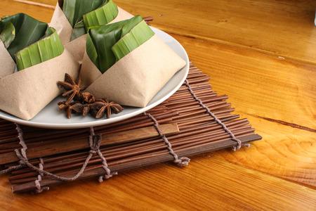 traditionele verse Maleisische nasi lemak die met banaanblad wordt ingepakt op houten achtergrond Stockfoto
