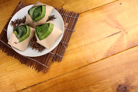 lemak: traditional fresh Malaysian nasi lemak packed with banana leaf in wood background