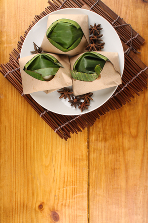 keropok: traditional fresh Malaysian nasi lemak packed with banana leaf in wood background