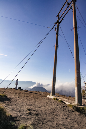 cinta: A local in the summit of Bukit Cinta Penanjakan, with an electrical cable in the foreground and mount bromo in the background