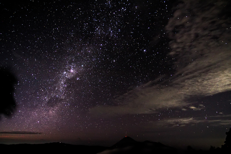 nebulae: milky way at mount bromo Indonesia with  small light coming from mount Semeru summit