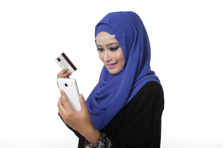 pelita: Malaysian malay asian woman using a smart phone or cell phone to shopping online
