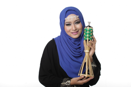 pelita: Malaysian malay woman holding a traditional oil lamp for eid isolated in white