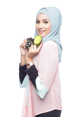 asian muslimah woman posing with a toy camera isolated in white background