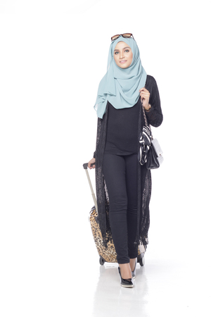 muslimah: muslimah asian woman with her trolly bag wating and posing for people isolated in white background