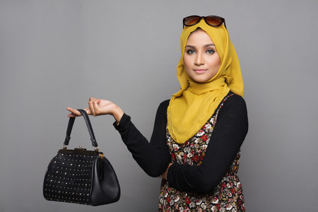 Muslimah woman posing with her handbag on gray background