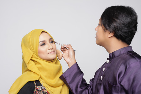 muslimah: muslimah woman being make up by make up artist