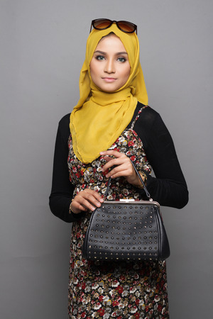 Muslimah woman posing with her handbag on gray background Banque d'images