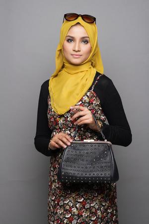 handbag: Muslimah woman posing with her handbag on gray background Stock Photo