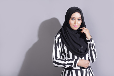asian beautiful muslimah woman with eid attire light with sun on gray background