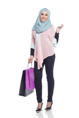 portrait of asian muslimah woman with her shopping bag having fun with toy camera in white background