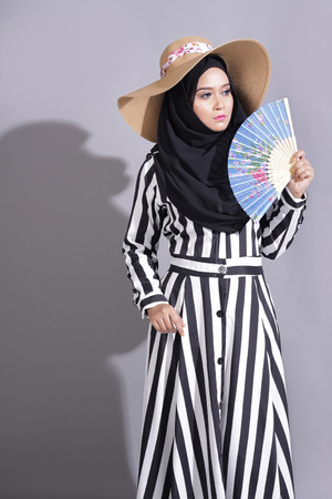 muslimah: asian beautiful muslimah woman with eid attire light with sun on gray background