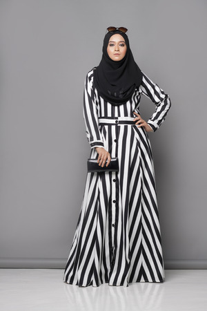Asian muslimah woman with beautiful attire on gray background