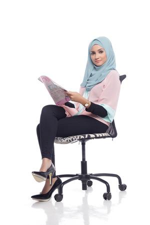 muslimah: portrait of young asian muslimah woman reading a magazine