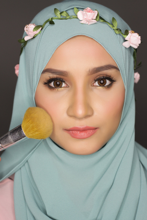 make over: portrait of young asian beautiful muslimah woman doing a make over on her face