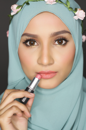 muslimah: portrait of young asian beautiful muslimah woman doing a make over on her face