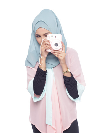 muslimah: asian muslimah woman posing with a toy camera isolated in white background
