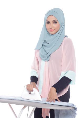 beautiful asian muslimah woman ironing in white background