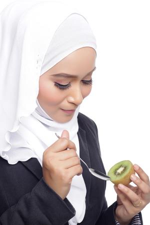 lifestile: asian beautiful muslimah woman eating healthy kiwi white background