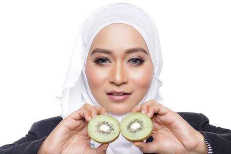 muslimah: asian beautiful muslimah woman eating healthy kiwi white background