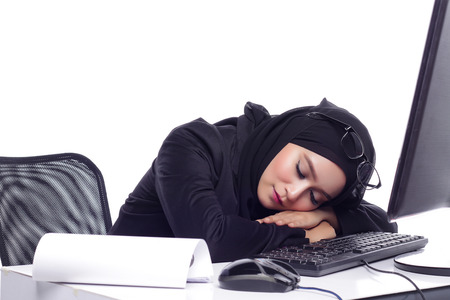 office attire: beautiful corporate muslimah woman with office attire showing tired expression while working on desktop computer Stock Photo