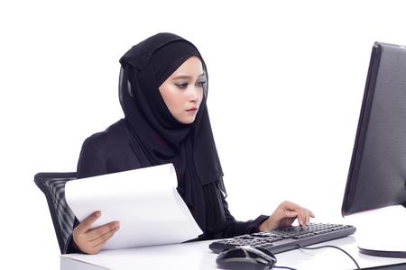 office attire: beautiful corporate muslimah woman with office attire working on desktop computer
