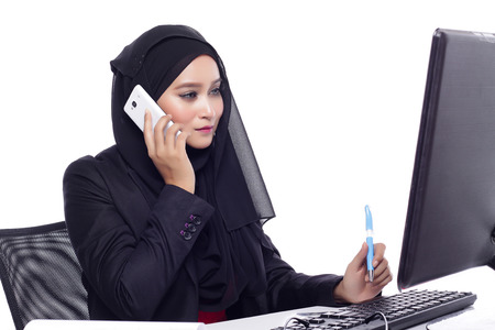 office attire: beautiful corporate muslimah woman with office attire on phone while at the office