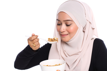 portrait of young asian woman eating cereals for breakfast in white background Banque d'images