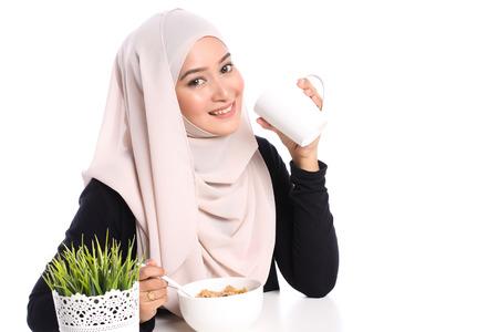 portret van jonge Aziatische vrouw het eten van granen voor het ontbijt in een witte achtergrond Stockfoto