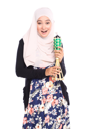 pelita: portrait of young malay woman in full shot posing with her dress while holding oil lamp or pelita isolated in white