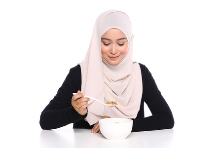 portrait of young asian woman eating cereals for breakfast in white background 版權商用圖片