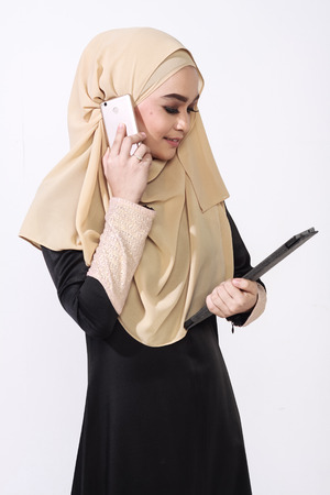 business matter: asian malay woman using a mobile phone while holding a tablet for business matter