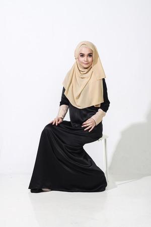 muslimah: beautiful malay woman sitting and posing with full muslimah attire on white background Stock Photo